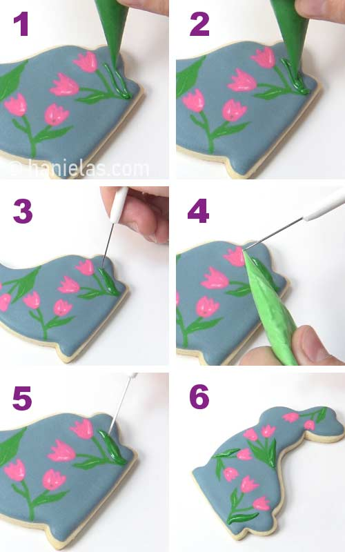 Piping a leaf with royal icing onto dry icing.