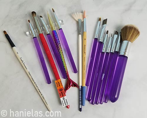 Variety of paint brushes laid out on a counter.