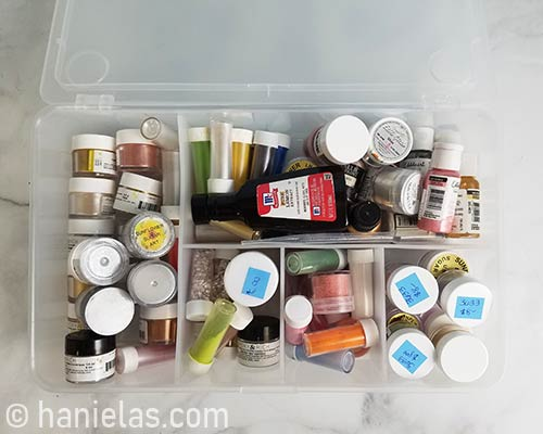 Luster dust, petal dust in small containers in an organizer.