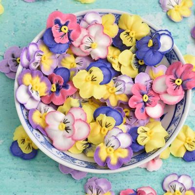 Colorful royal icing piper pansy flowers in a small bowl.