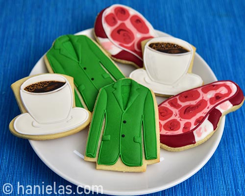Collection of decorated green suit jacket, steak and coffee cup cookies on a plate.