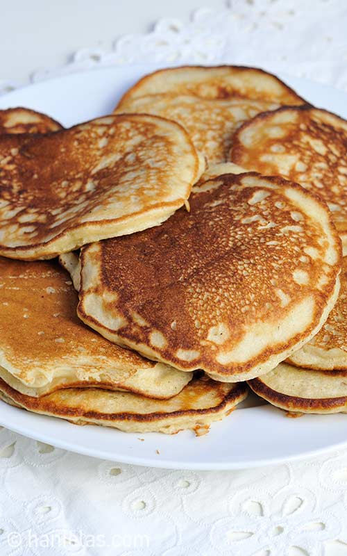Close up of cooked pancakes stacked on a plate.