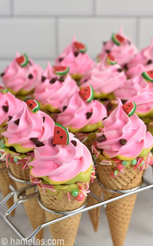Pink meringue ice cream cone cookies nested in a baking stand.