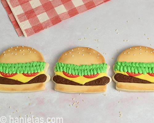 Royal icing decorated hamburger cookies on white background.