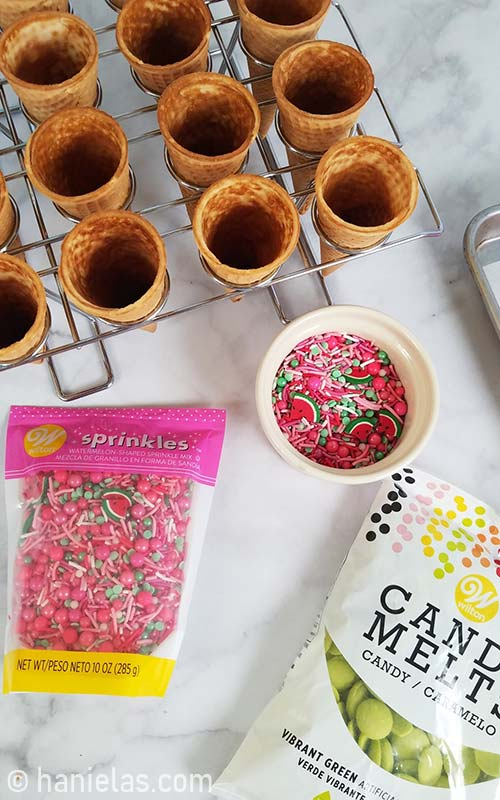 Ice cream cones nested in a baking rack, colorful sprinkles in a bowl.
