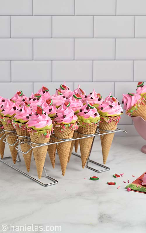 Pink meringue ice cream cone cookie nested in a baking rack.