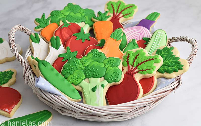 Decorated sugar cookies that look like vegetable in a white basket.
