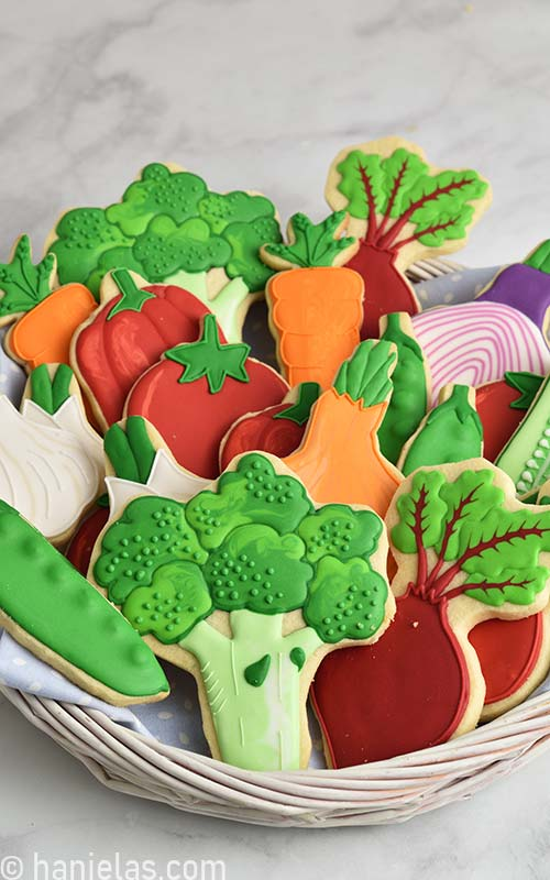 Cookies decorated with royal icing that look like vegetables displayed in a white basket.
