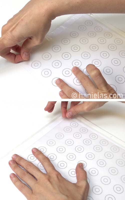 Taping wax paper onto a donut template.