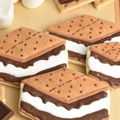Cookies decorated to look like s'mores displayed on a wooden board along with marshmallows and chocolate pieces.