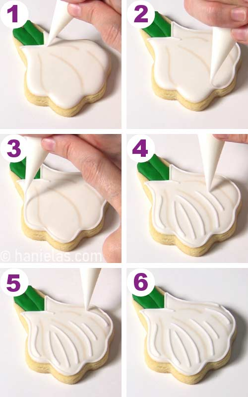 Outlining a garlic shaped cookie with white icing.