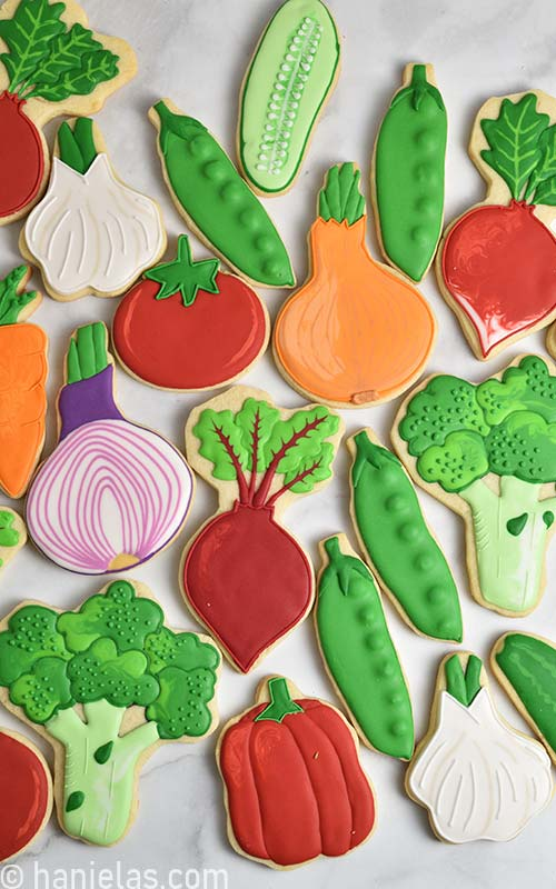 Cookies decorated with royal icing that look like vegetables on a marbled kitchen counter.