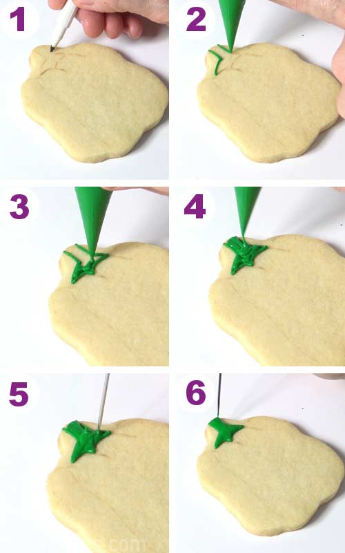 Piping a stem with green icing onto a bell pepper shaped cookie.