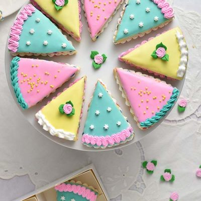 Decorated wedge cookies that look like little cakes on a cake stand.
