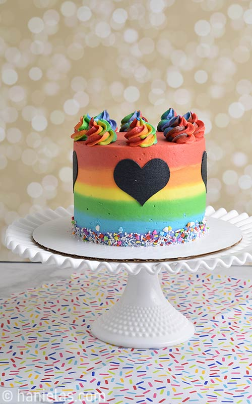 Cake decorated with rainbow buttercream stripes displayed on a cake stand.