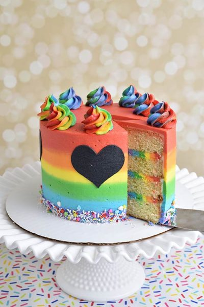 Decorated rainbow buttercream cake on a cake stand.