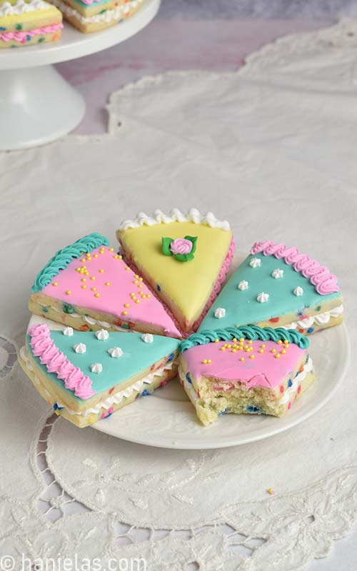 Decorated cookie that look like cake slices on a white plate with one cookie bitten.