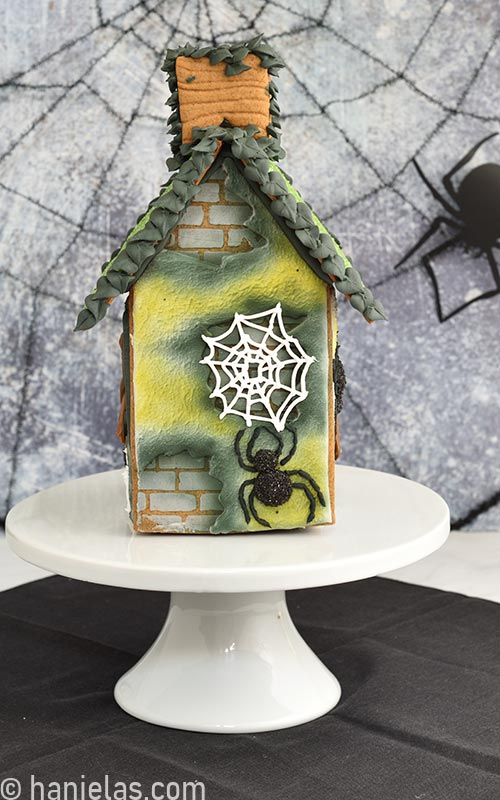 Gingerbread house decorated with black spiders on a white cake stand.