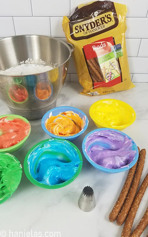 Colored meringue into small bowls on a counter.