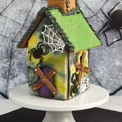 Halloween decorated gingerbread house displayed on a white cake stand.