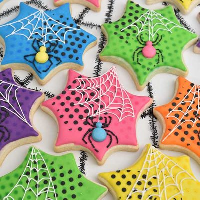 Spider web shaped decorated cookies with royal icing spiders and white spider web.