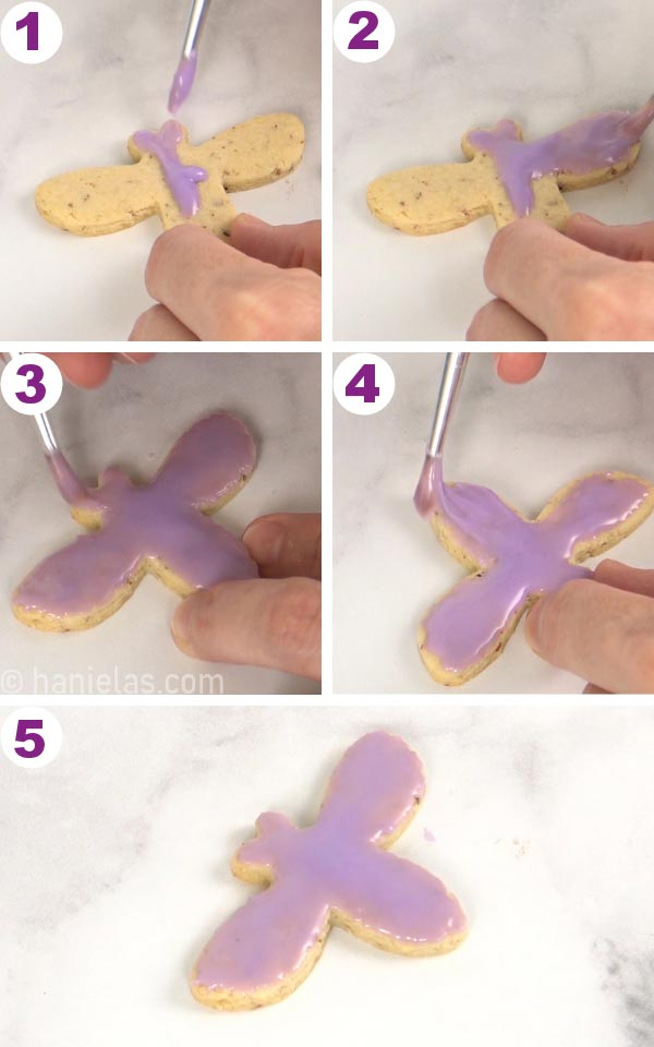 Spreading glaze icing onto a cookie with a paint brush.