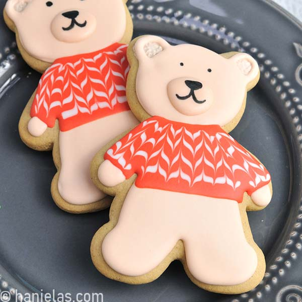 Light brown bear cookie decorated with royal icing on a gray plate.