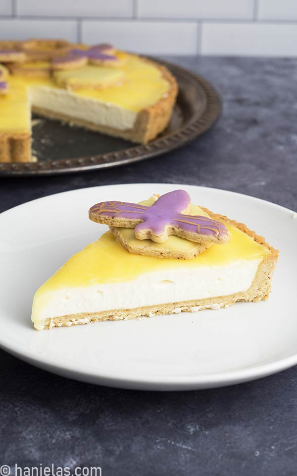 Slice of a cheese cake with a lemon curd topping on a white plate.