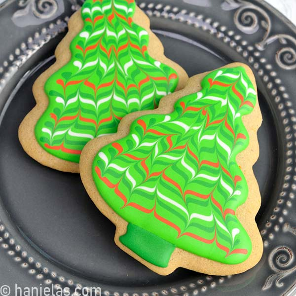 Tree cookie decorated with marbled wet on wet royal icing design.