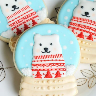 Snow globe cookies decorated with royal icing on a pretty white and silver plate.