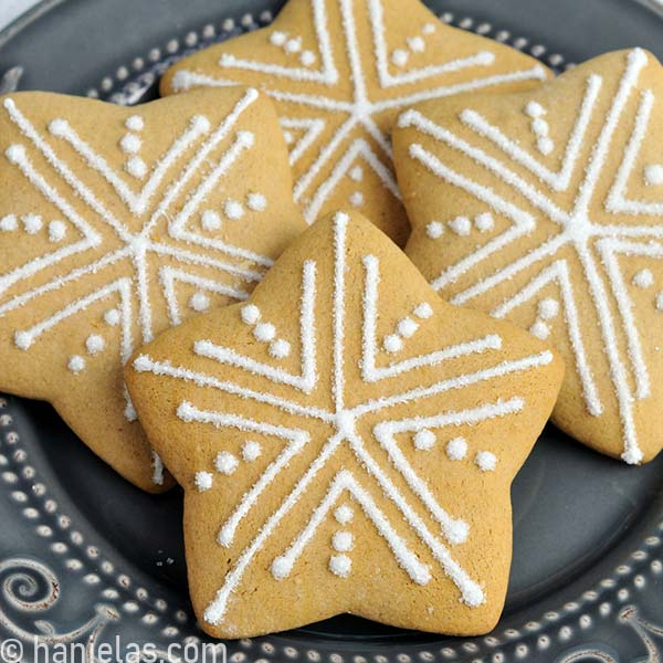 Star cookie decorated with simple white snowflake like pattern.
