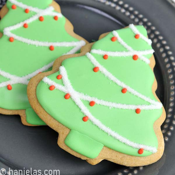 Tree cookie decorated with light green icing, white garland dipped in sanding sugar and red polka dots.