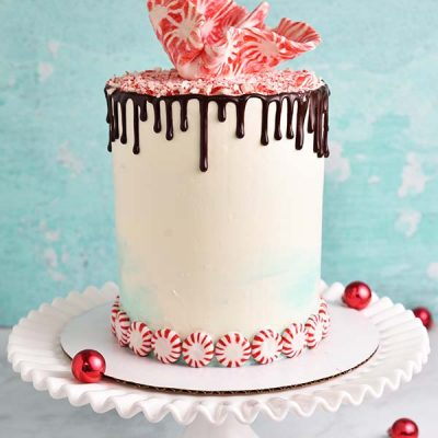 White and teal buttercream cake decorated with peppermint candies, cake sale and chocolate drips.