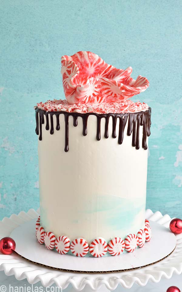 White cake with chocolate drips decorated with crushed peppermint candies on a white milk glass cake stand.