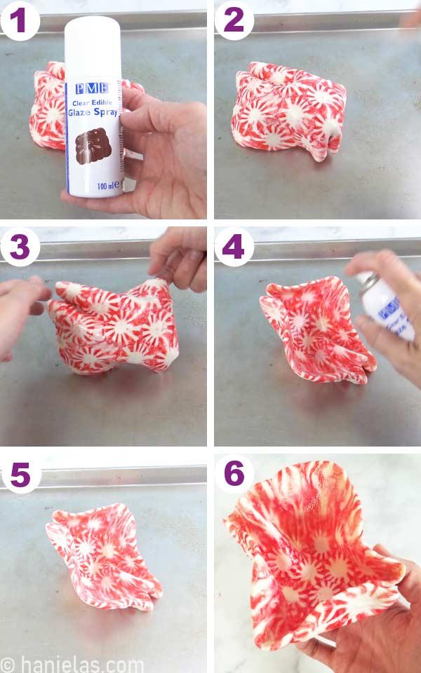 Candy cake sail on a baking sheet, spraying cake sail with a PME glaze spray.