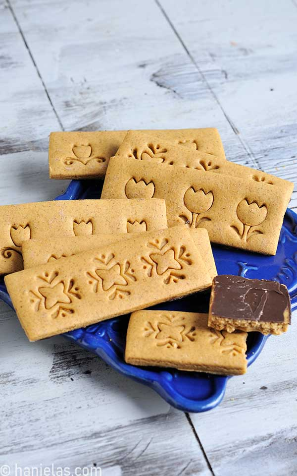 Cookies stamped with a decorative designs displayed on a blue plate.