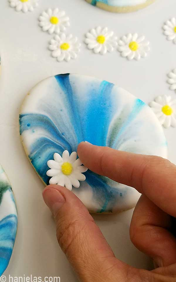 Attaching sugar flower on blue marbled Easter egg cookies.
