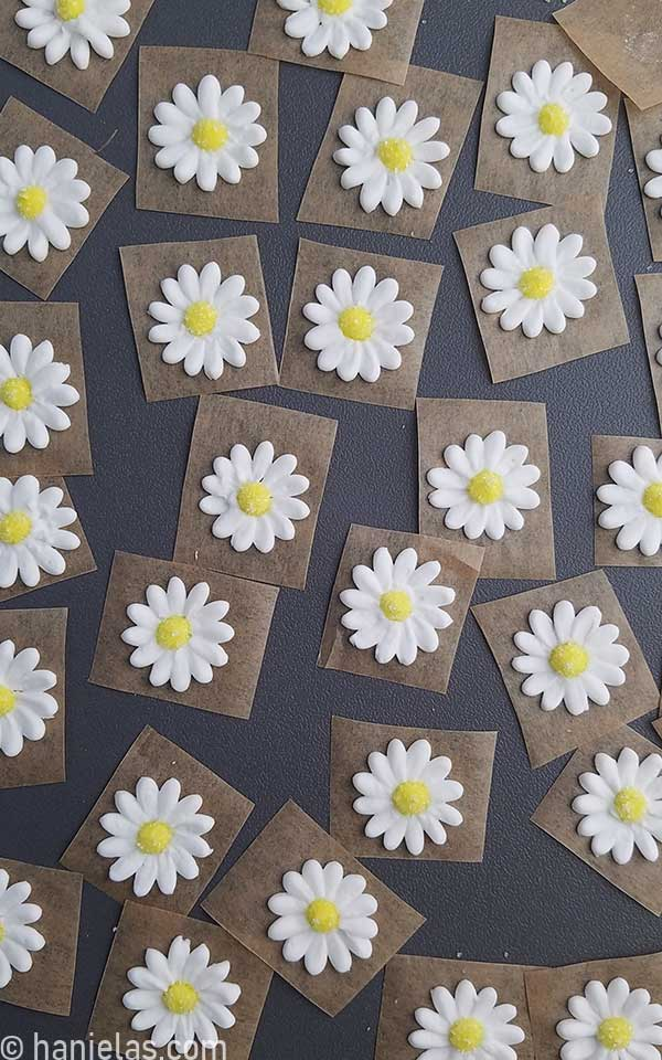 Piped royal icing flowers parchment squares, drying on a gray tray.
