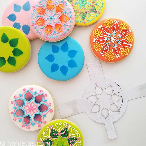 Decorated cookies on a white background, cardstock stencil on the side.
