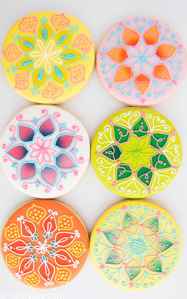Colorful mandala inspired cookies on a white background.