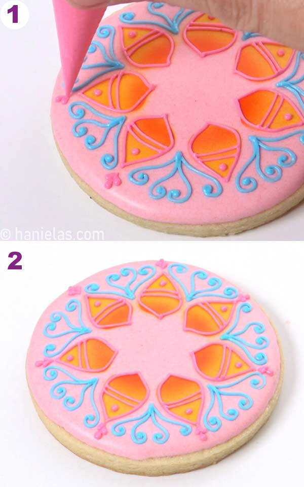 Piping teardrop shapes with royal icing on to a cookie.