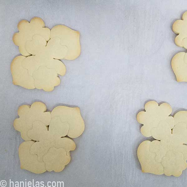 Baked cookies constructed from several cookie cutters on a parchment lined baking sheet.