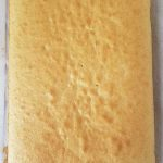 Baked yellow cake on parchment paper.