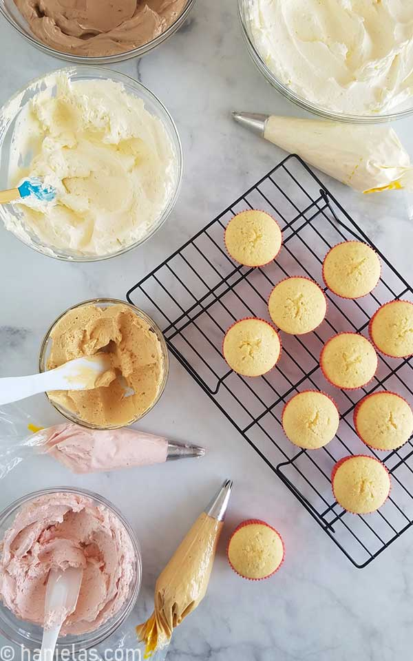 Undecorated cupcakes and buttercream in bowls on a marbled counter top.
