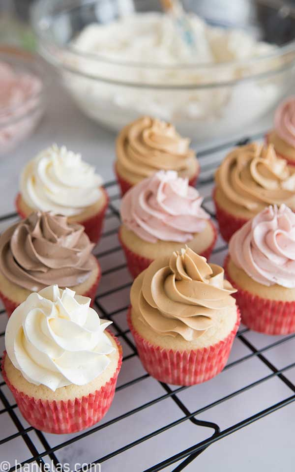 Cupcakes decorated with a buttercream swirl on a black cooling rack.