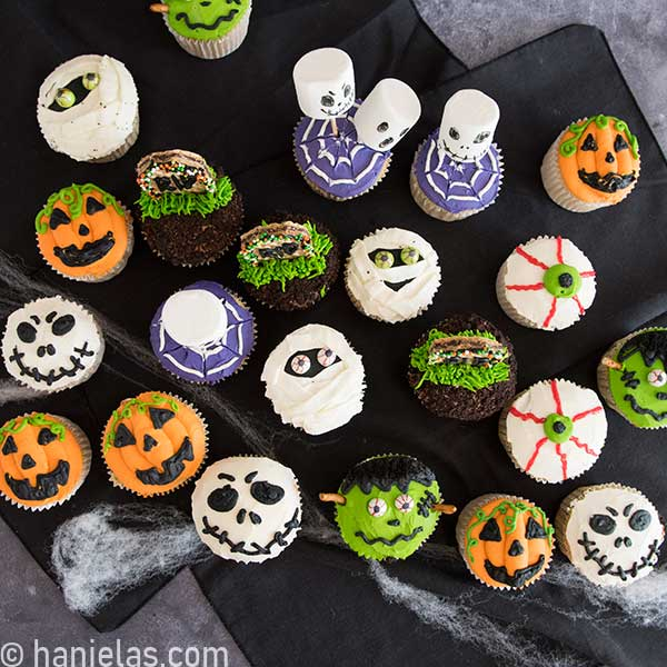 Variety of Halloween decorated cupcakes displayed on a black tablecloth.