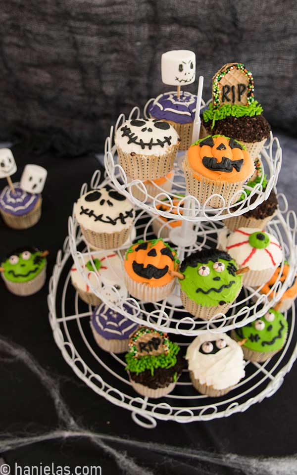 Cupcakes decorated with buttercream displayed on white wire cupcake stand.