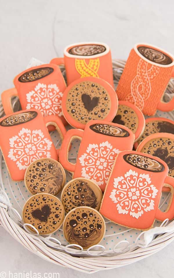 Coffee mug cookies nested in a white basket.
