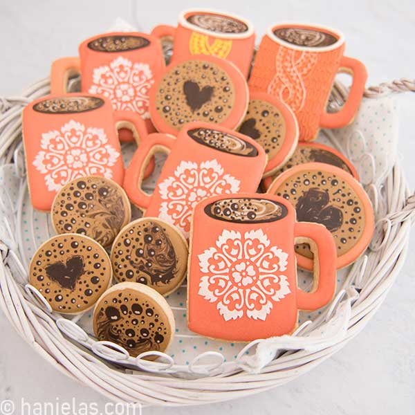 Decorated coffee mug cookies, and rounds with coffee bubbles designs, nested in a white basket tray.
