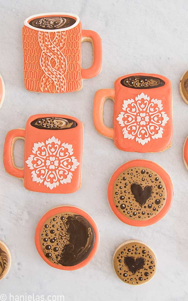 Decorated coffee mug cookie with coffee bubbles and stenciled design.